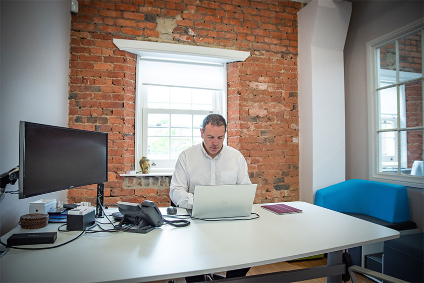 Owner of business at desk with laptop